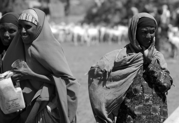Women talk as their animals drink in East Africa.