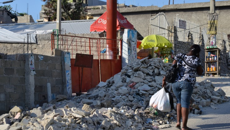 A woman walks by rubble after shopping in Delmas 18, Port au Prince.