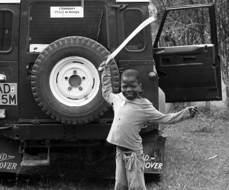 A child playfully brandishes a machete during Kenya's post-election crisis.