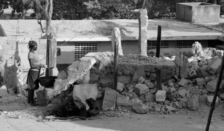 A woman stands next to a destoyed house in Port au Prince, Haiti.