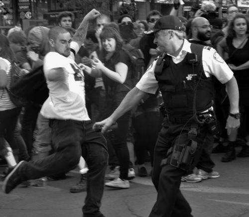 A protester kicks a police officer during student protests in Montreal.