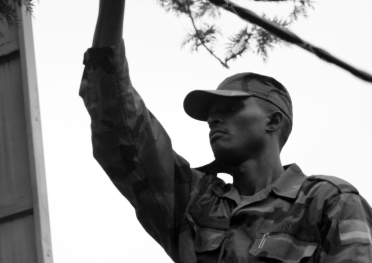 A soldier swings a baton during the Rwandan pull-out from mineral-rich Eastern DRC