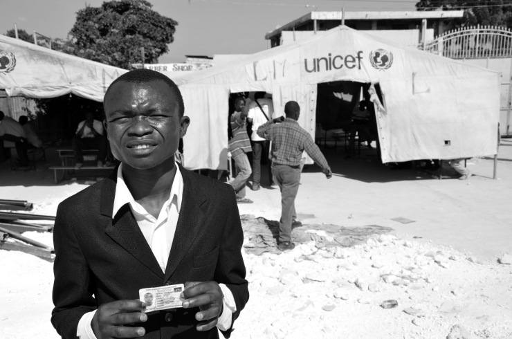 A man shows his voter card in the Cite Soleil slum on election day, 2011