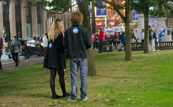 A couple quietly watch in George Square, Glasgow as the results of the referendum filter in.