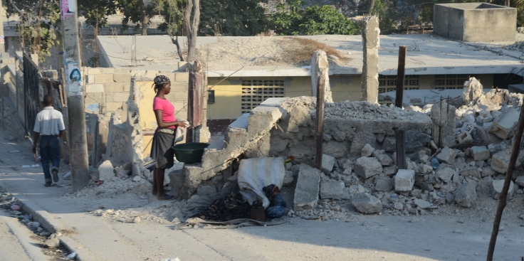 A woman looks over a collapsed house. Much of Haiti was destroyed by the 2010 earthquake.