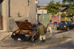 A man washes a car in Port au Prince, Haiti in the aftermath of the earthquake that devastated much of the country.
