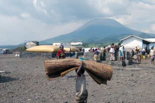 A child carries a bed-roll through the Kibati II refugee camp in Eastern Congo.